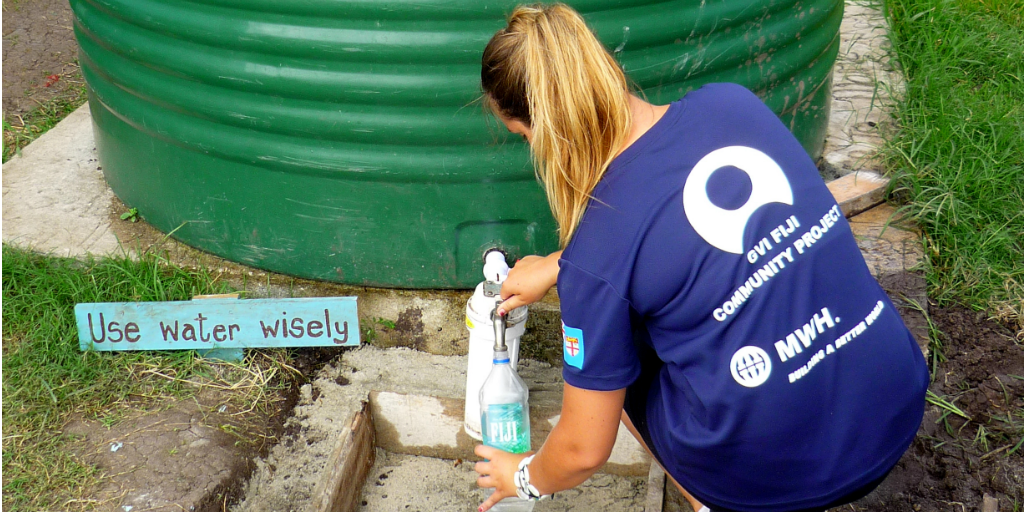 A volunteer filling a water bottle from a rain harvesting water tank.