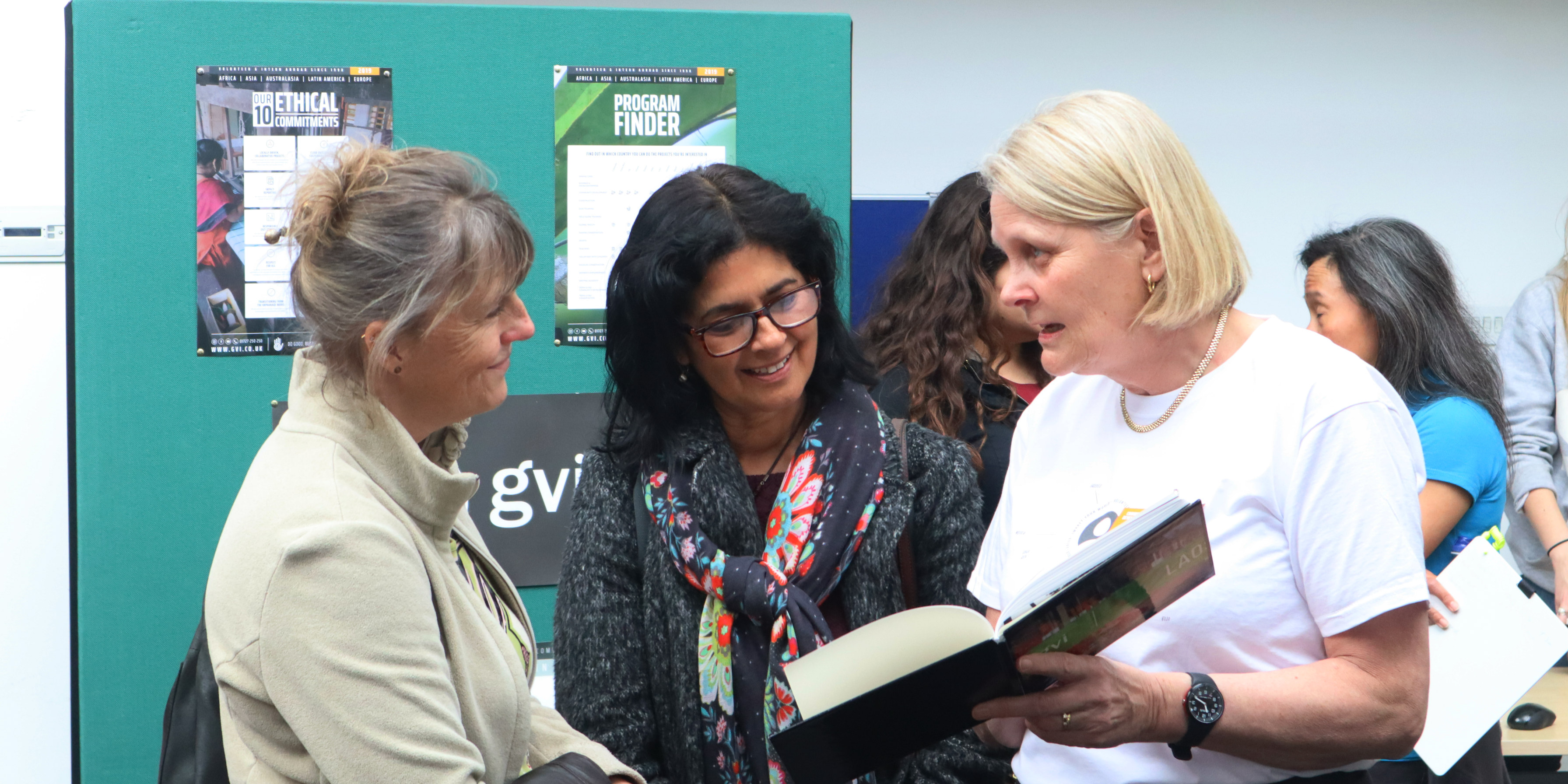 A GVI ex volunteer showing two interested women a page in a book.