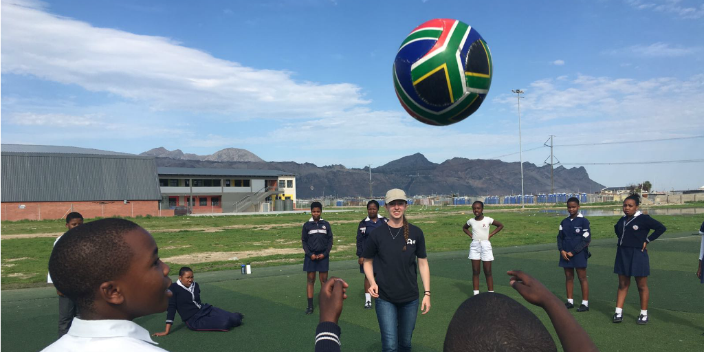 A volunteer facilitating a soccer lesson with children in South Africa.