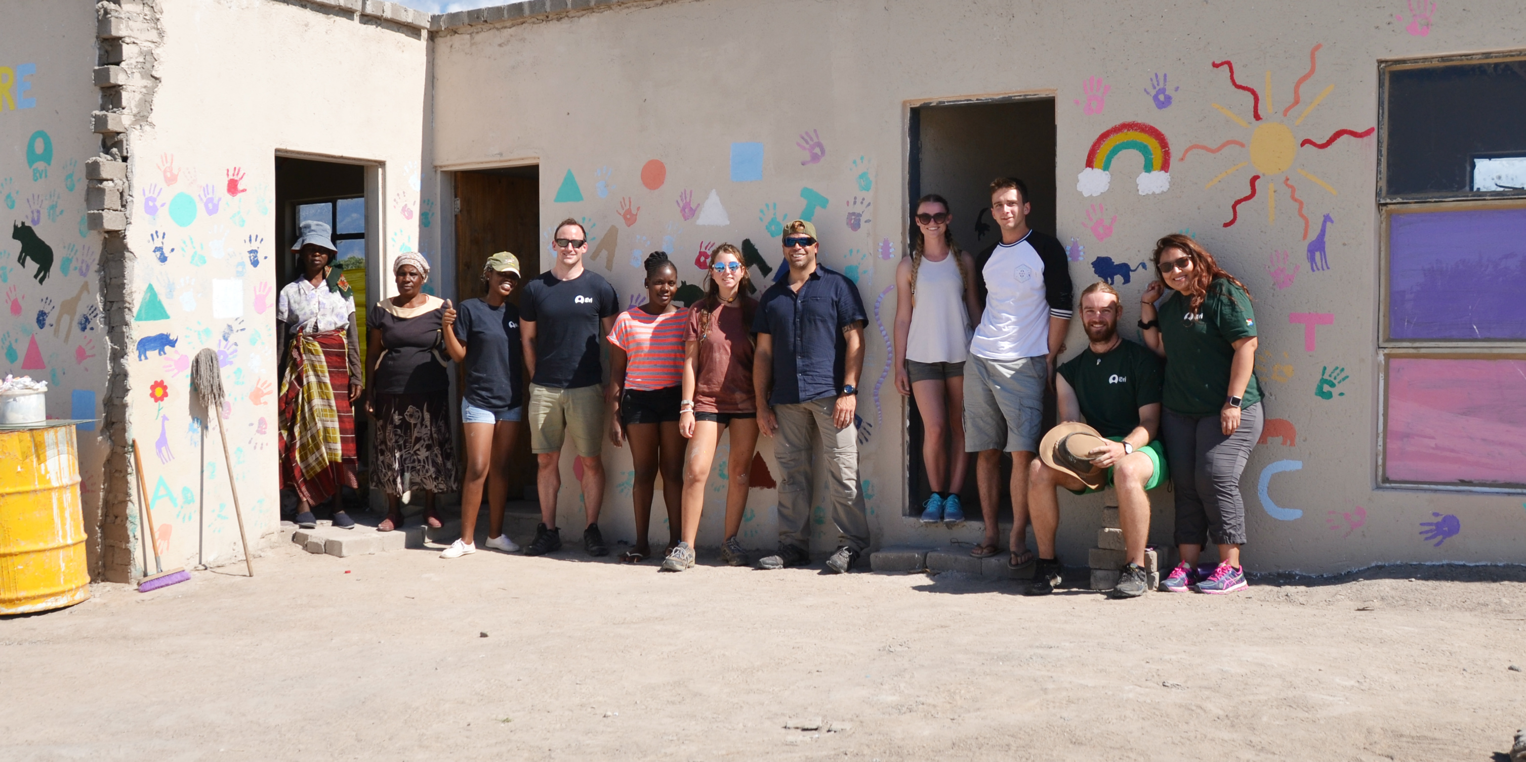 While volunteering in Africa with animals, GVI participants took time from their research to improve facilities at a local creche. Pictured: GVI participants and creche owners stand in front of the finished kitchen.