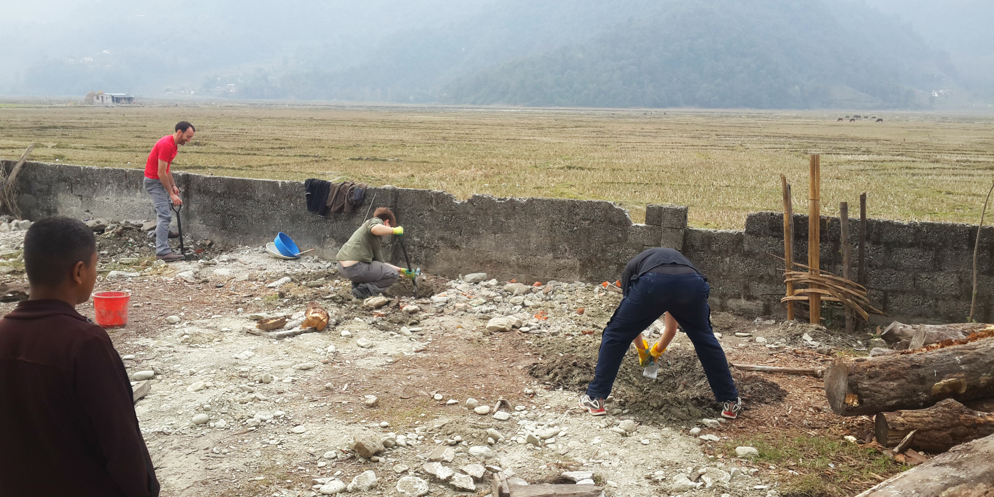 While volunteering in Nepal, participants build a wall around a school, to help ensure the good health and wellbeing of the learners.