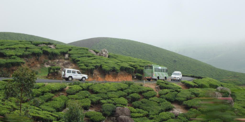 Vehicles driving along a dirt road on a green hillside.