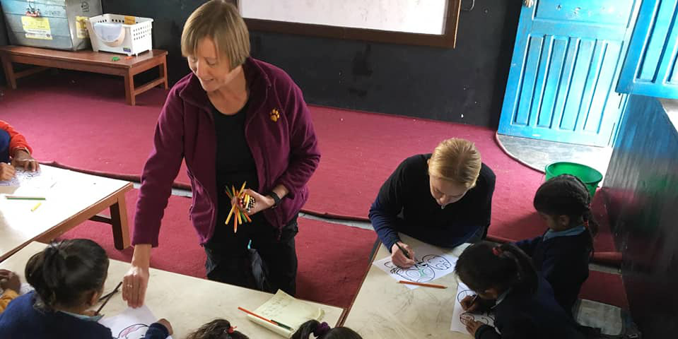 An adult volunteer distributes school supplied to learners in Nepal. As an older adult, you can really make an impact on top volunteer abroad programs.