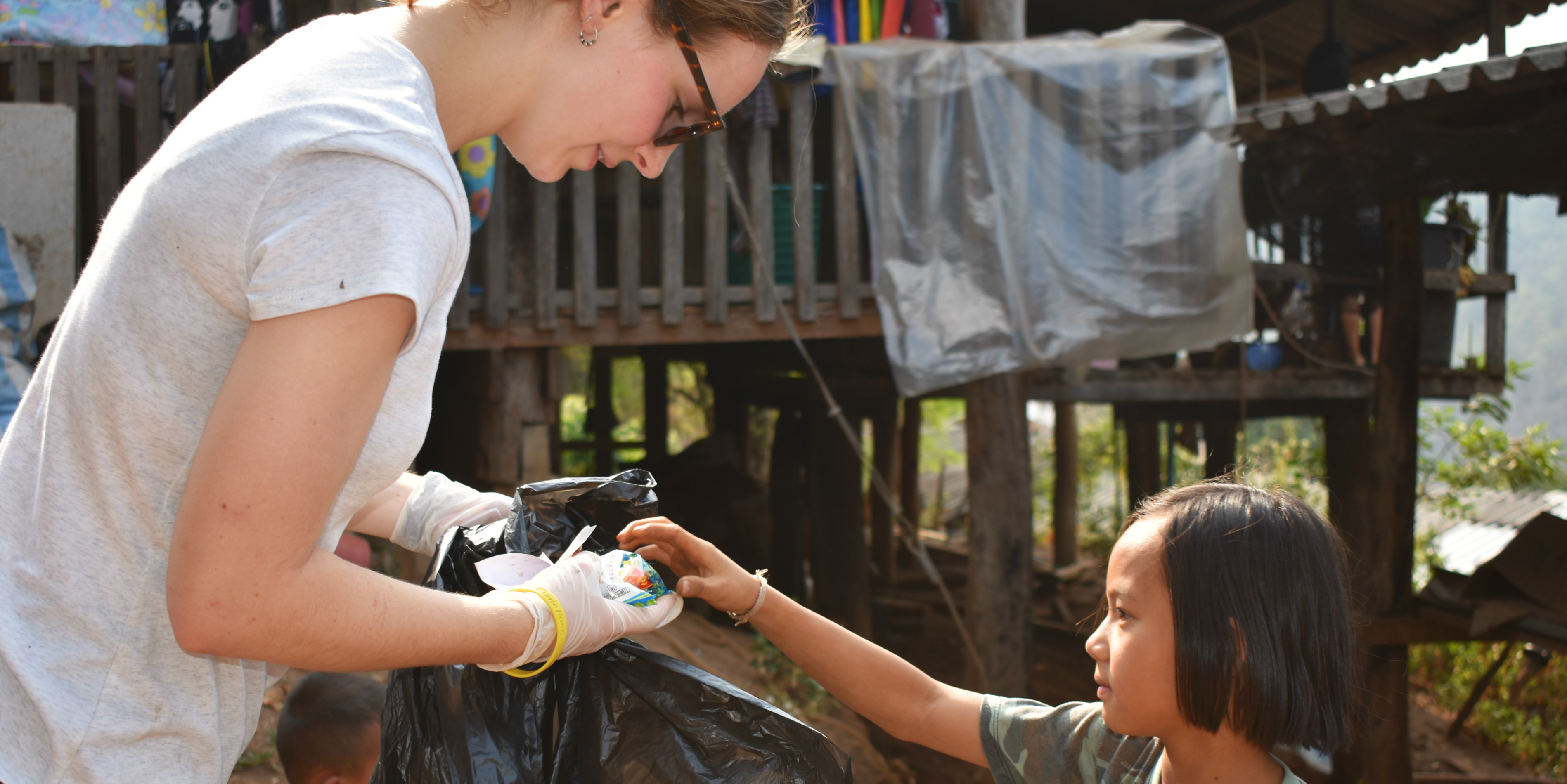 A GVI participant collects plastic waste in Chiang Mai, Thailand, with the help of a young girl. In between working to collect behavioral data on elephants in Thailand, participants work on environmental education initiatives.