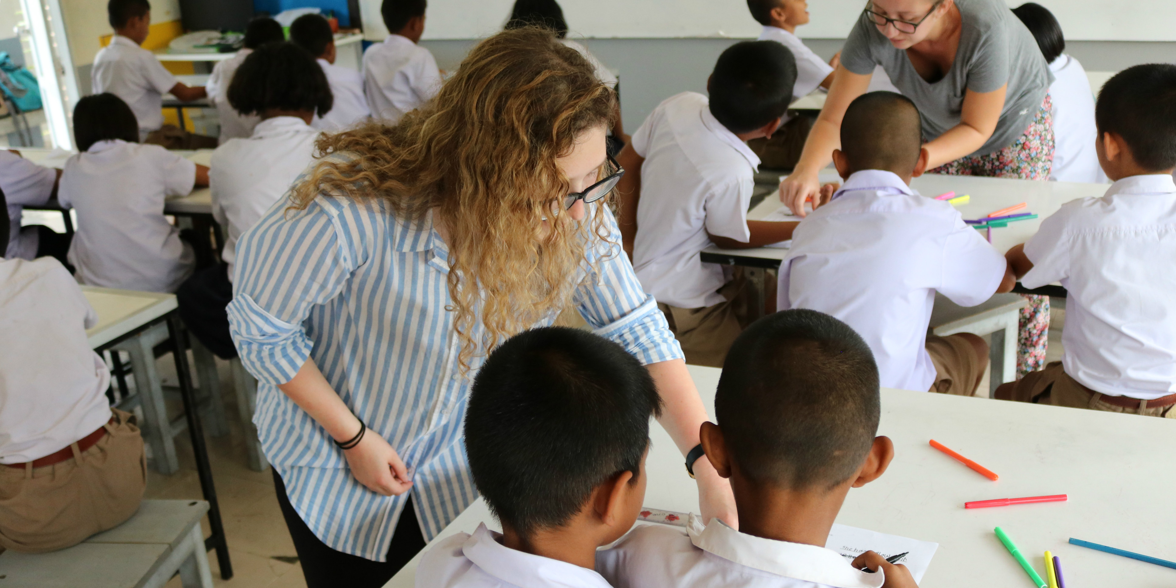 After completing their TEFL training with GVI, a participant assists learners in a school in Thailand.