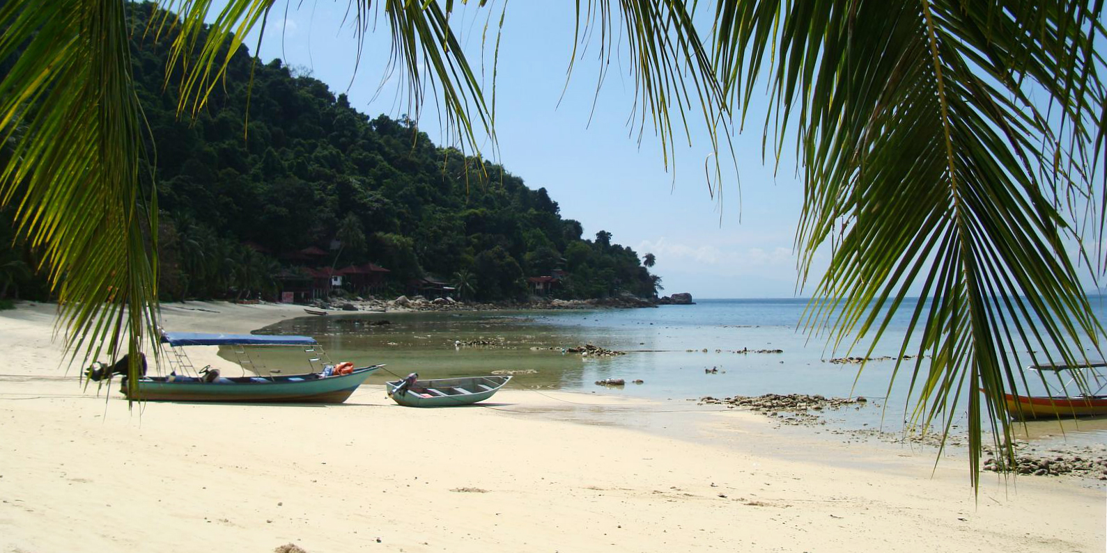 An idyllic scene of a wooden fishing boat on a Perhentian Island beach.