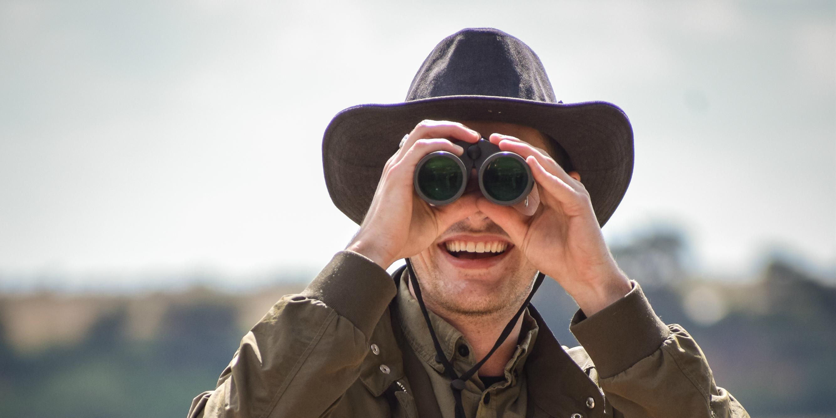 A wildlifer conservation participant looks through binoculars.