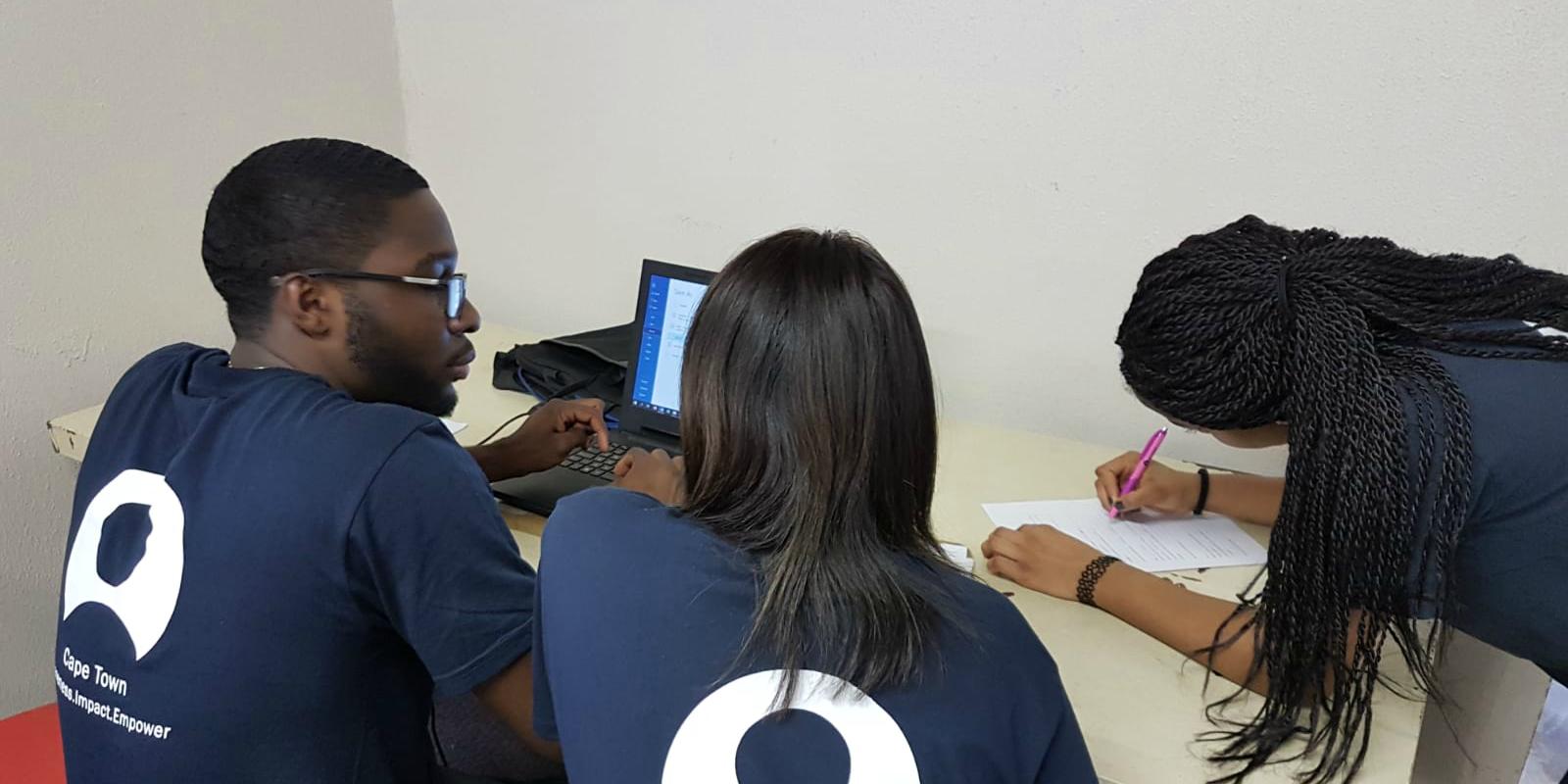 GVI participants plan lessons for the women's empowerment program on computer literacy.