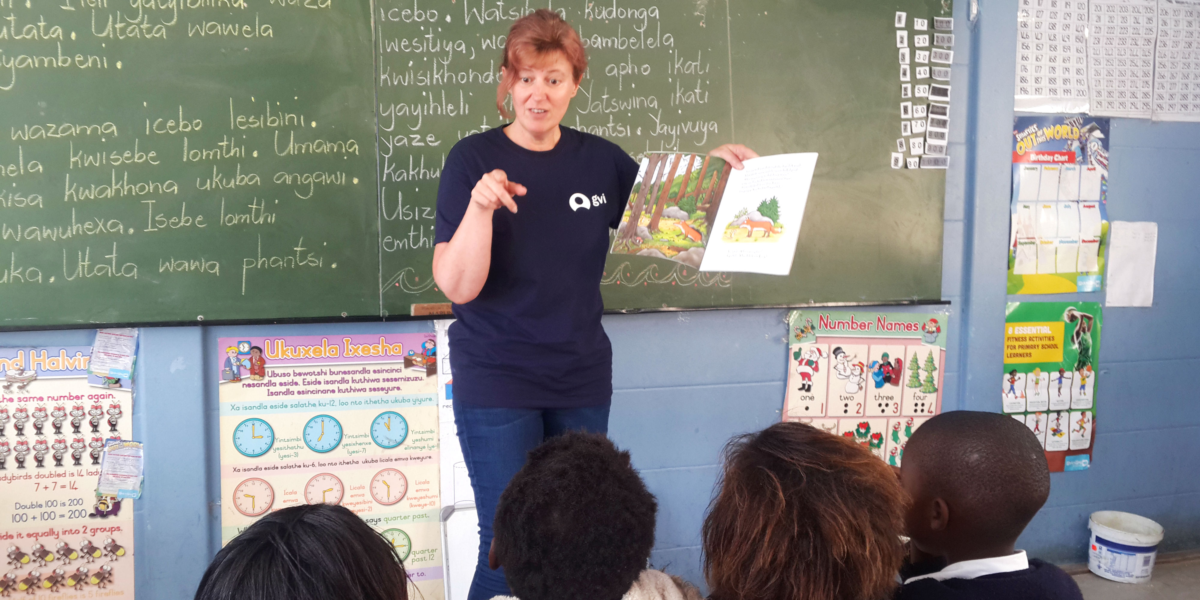 A GVI volunteer in South Africa reads a story to young learners. Education initiatives form an important part of promoting gender equality in education.