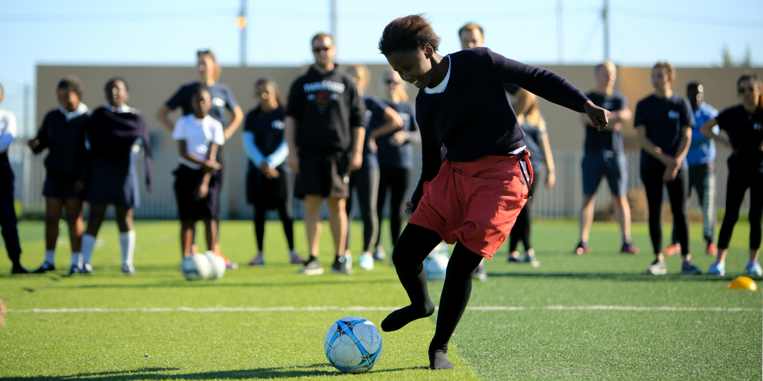 A young woman dribbles a soccer ball at a GVI sports program in Cape Town.