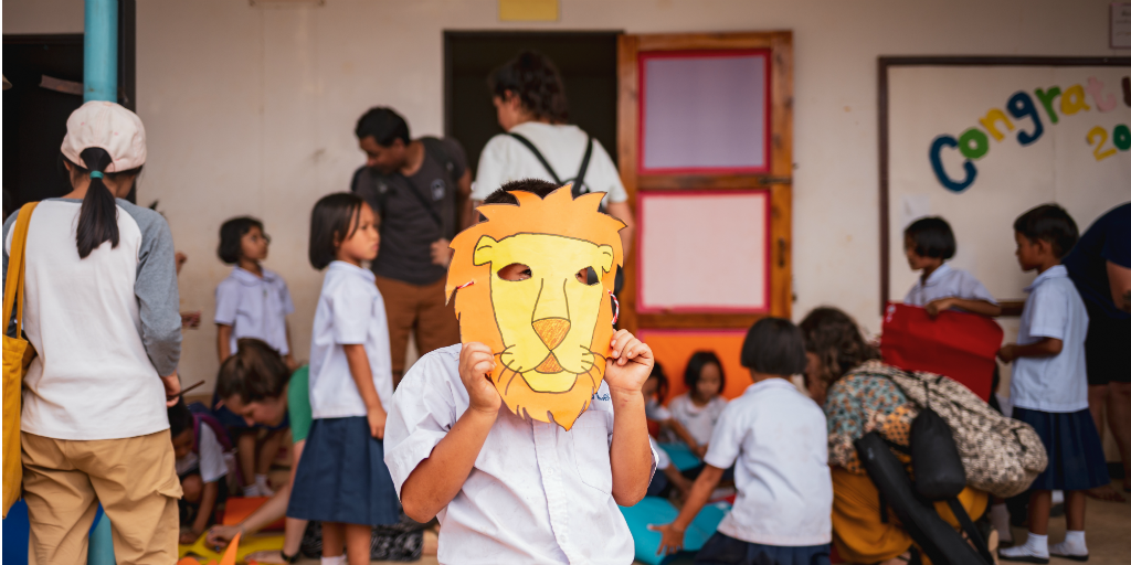 A child wearing a lion mask
