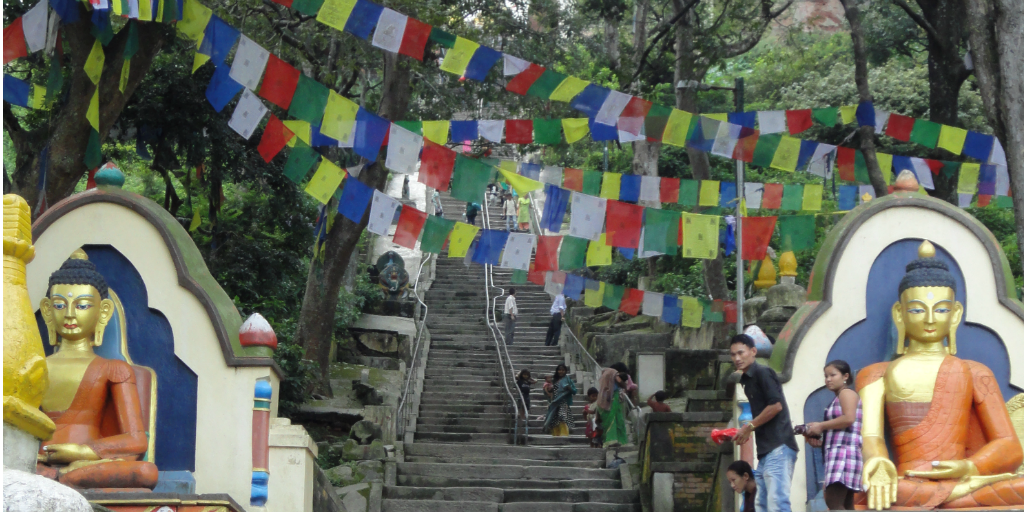 Stairs with religious statues on either side and flags hanging overhead