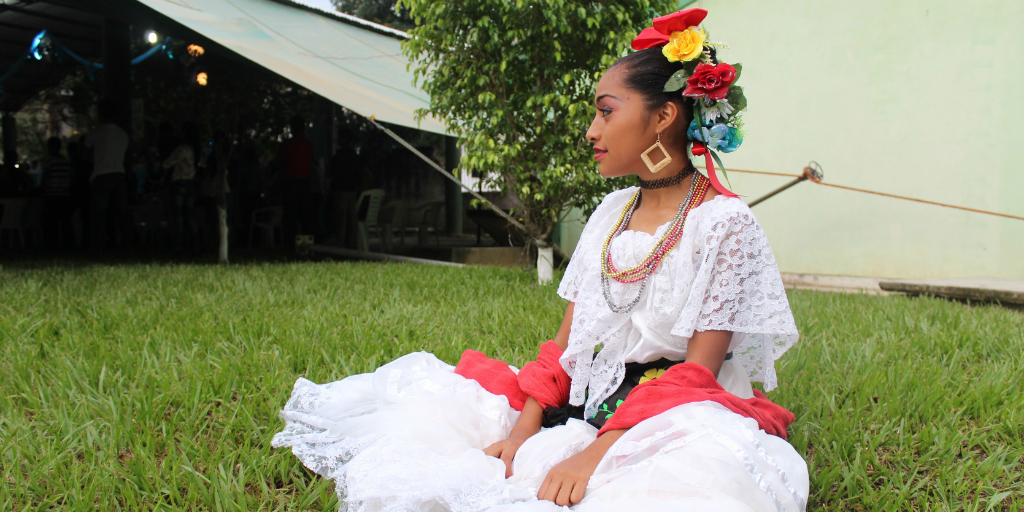 A Mexican woman in traditional dress sitting on grass.