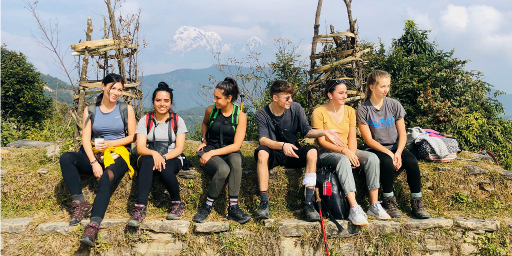 A group of volunteers taking a break on a hike in Nepal.