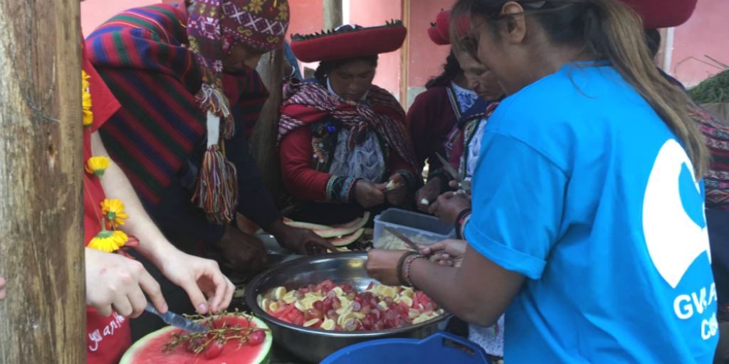 Community volunteers in Peru helping local Peruvian women cook