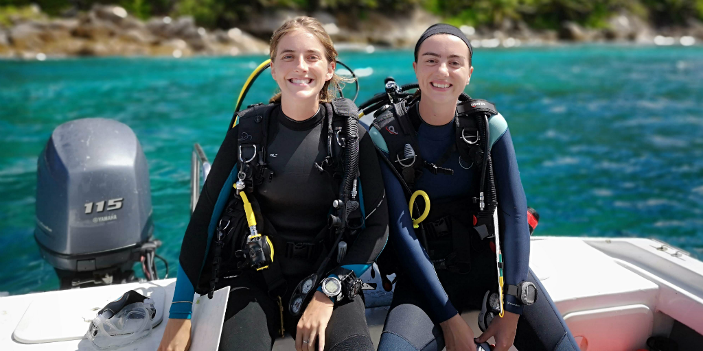 Two divers wearing their scuba gear and sitting on the edge of a boat.
