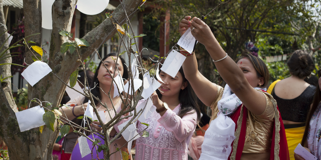 Nepalese women hanging decorations in a tree.