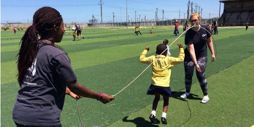 Volunteers swinging a skipping rope while a child jumps over the rope.