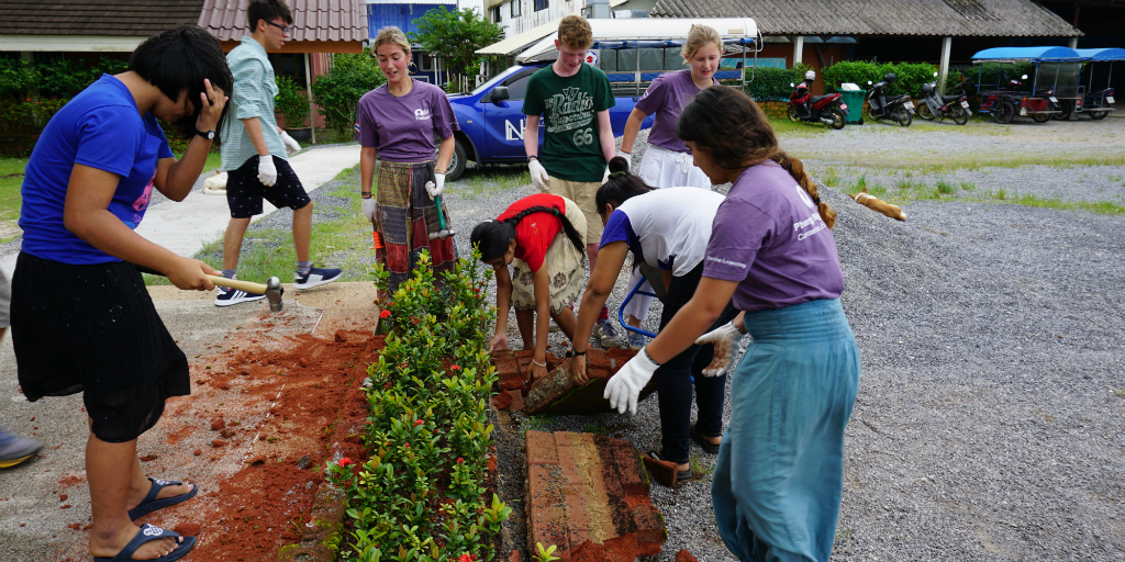 Teen volunteers working on community development garden installments in Thailand